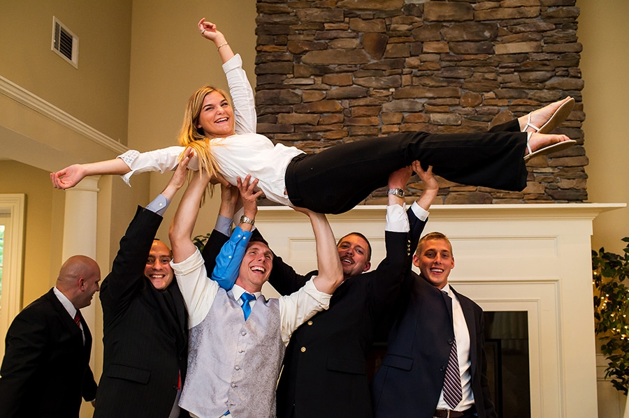 Photographer's assistant lifted into the air by the groomsmen.
