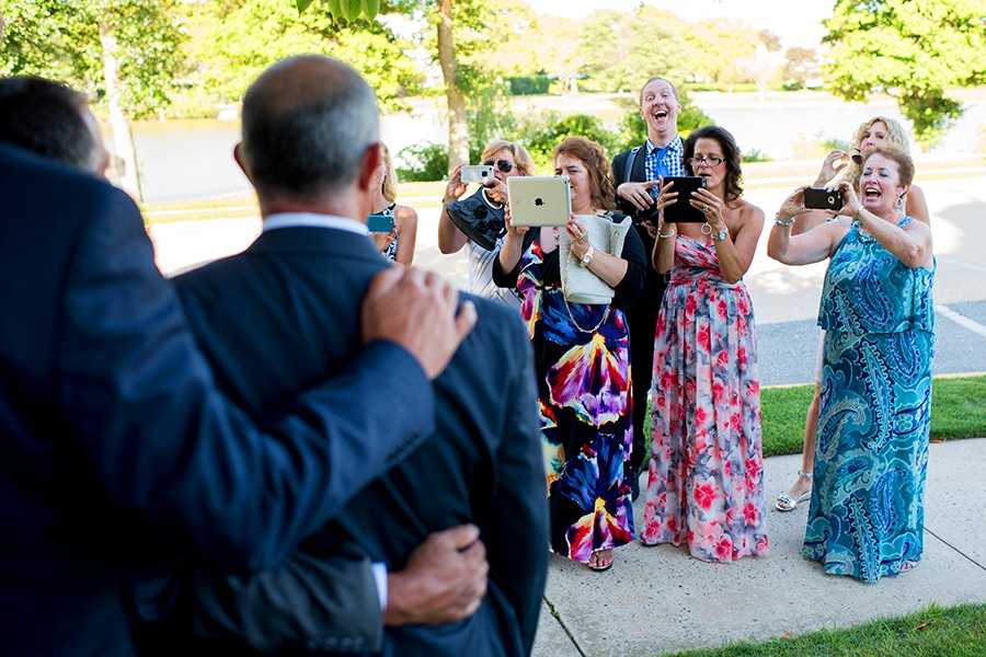 Photographer standing behind weddings guests taking photos.