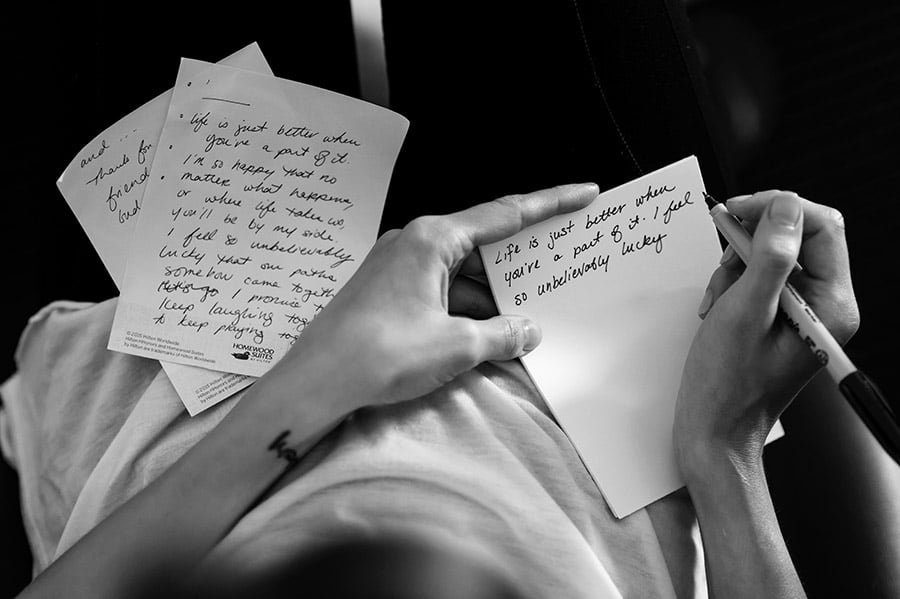 Bride writes out wedding vows on wedding morning.