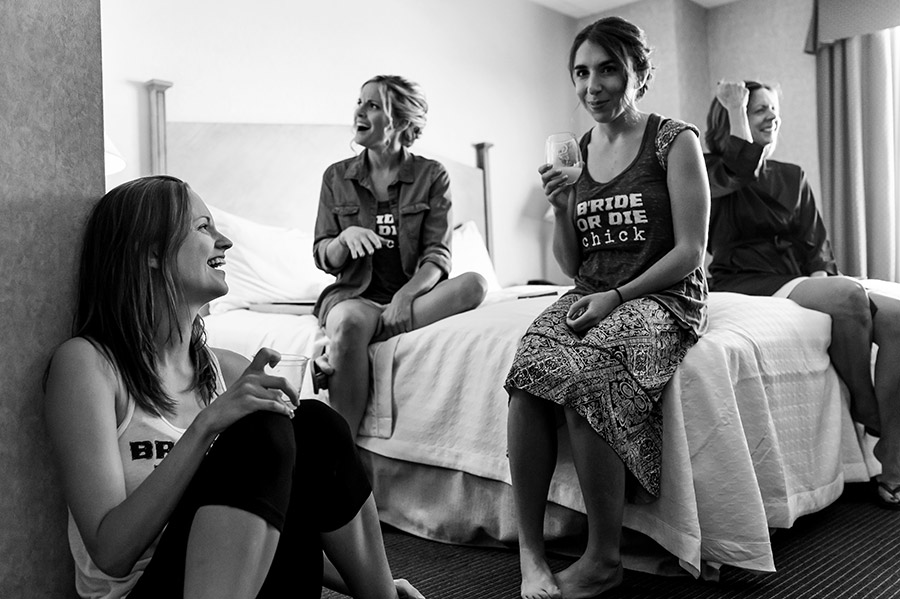 Bride and bridesmaids laugh while they get ready on wedding day.