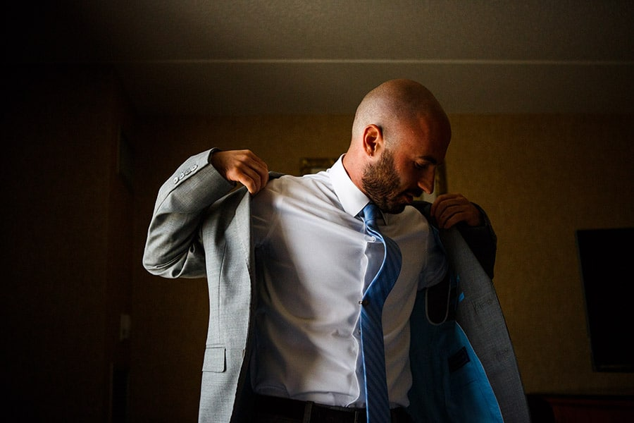 Groom put his suit jacket on on his wedding day.