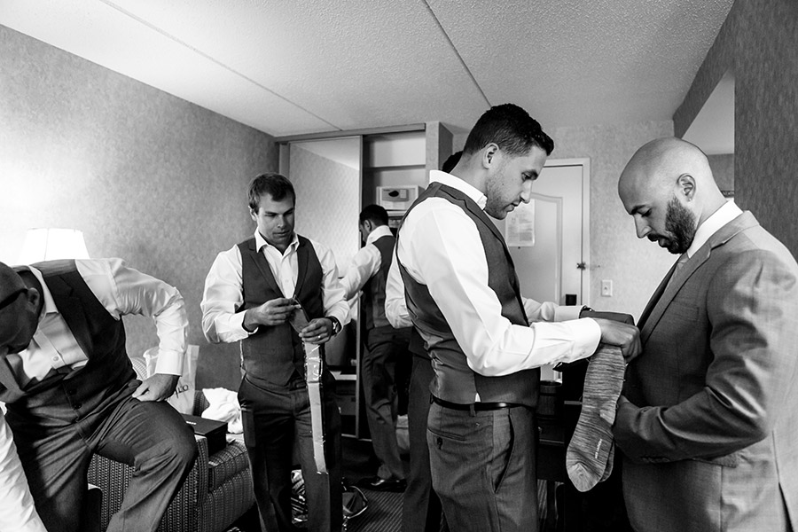 Groomsmen helps groom with tie.