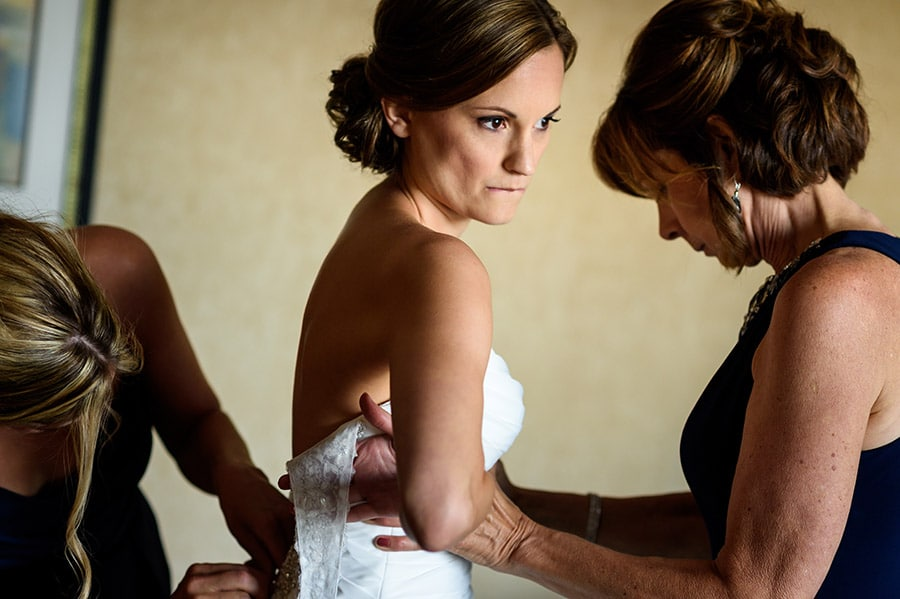 Nervous bride puts her gown on.