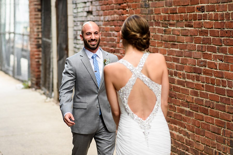 Excited groom sees bride for first time at first look.