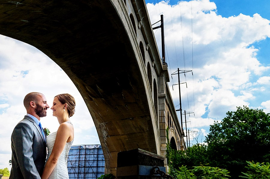 Bride and groom under a bridge on wedding day.