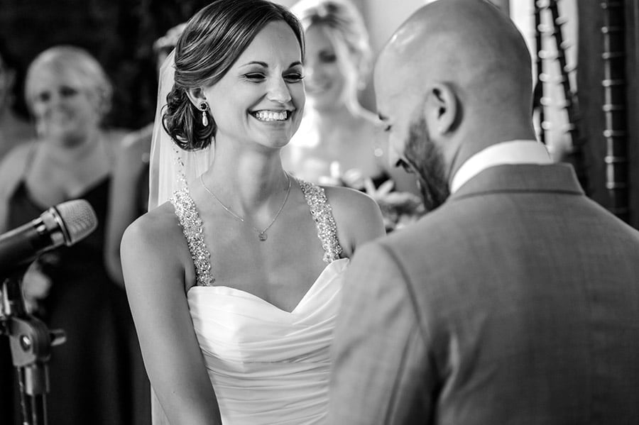 Bride smiles at emotional groom.
