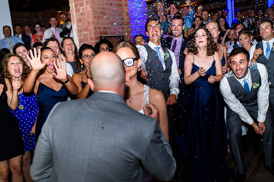 Weddings guests throw confetti at bride and groom as they enter reception.