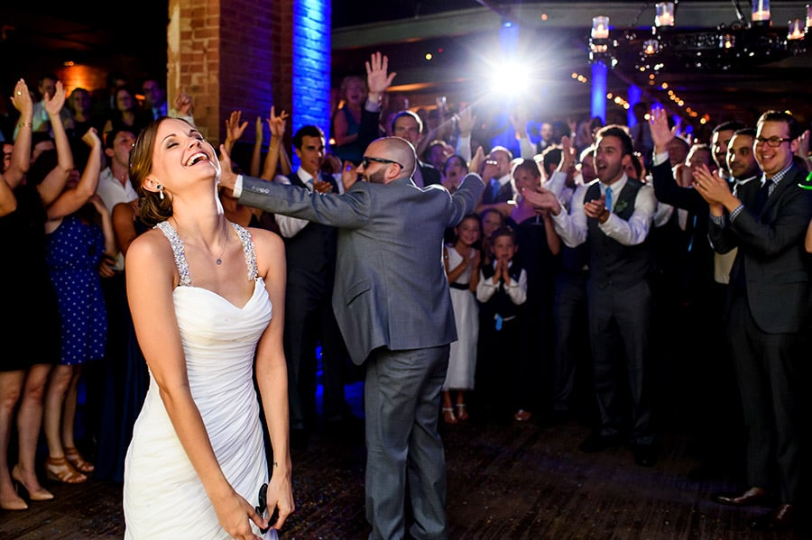 Bride laughs as groom entices weddings guests.