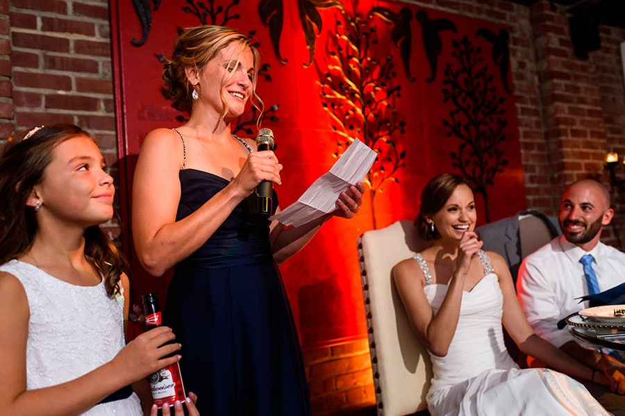 Bride and groom laugh at maid of honor during wedding speech.