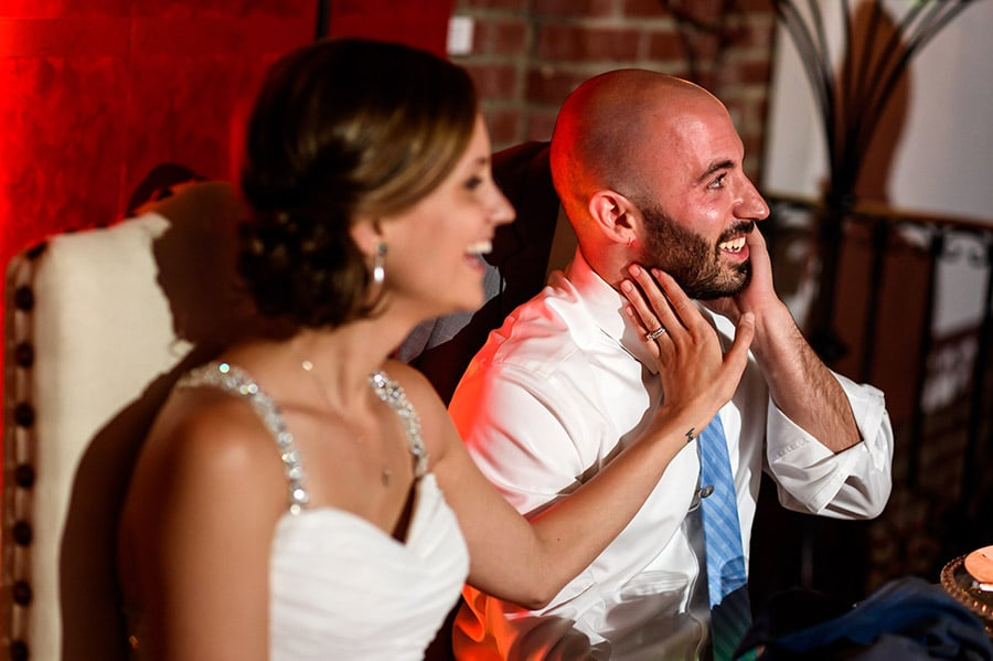 Bride touches groom on the face during wedding speeches