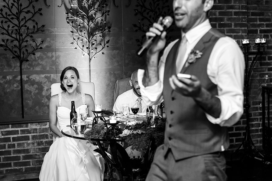 Bride and groom laugh hysterically at Best Man speech.