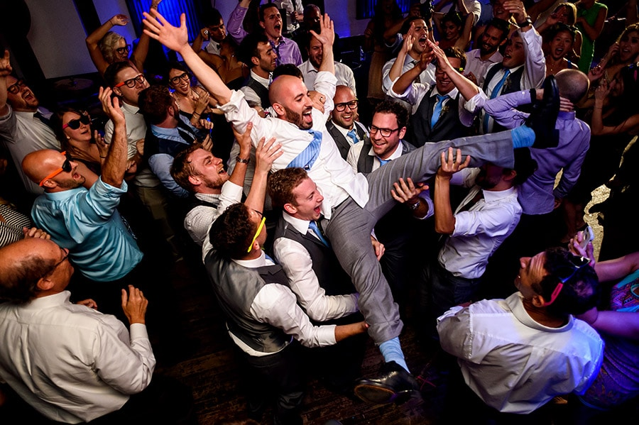 Groomsmen throw groom into air during wedding reception.