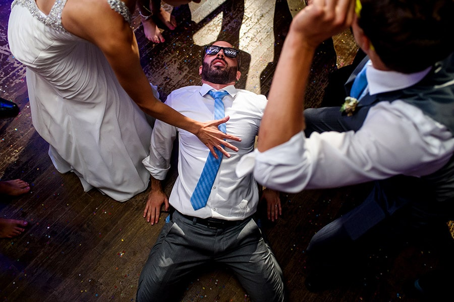 Groom lays on dance floor.