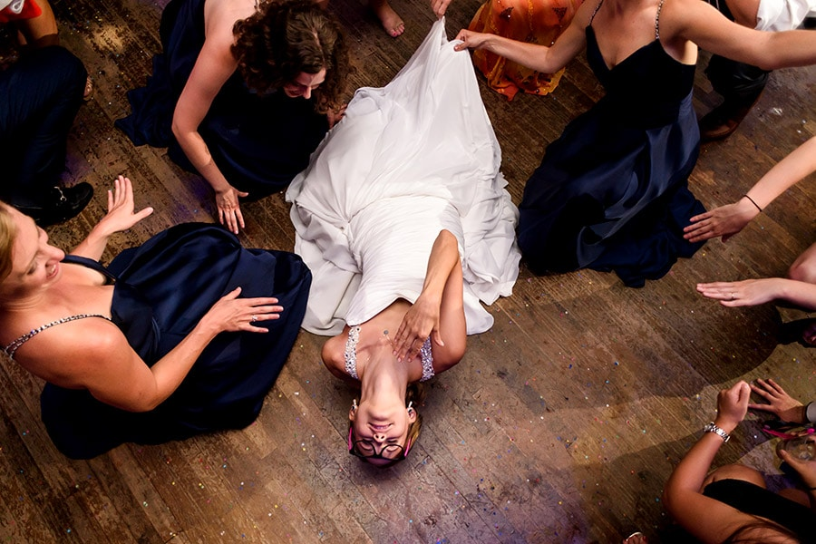 Bride lays back on dance floor.