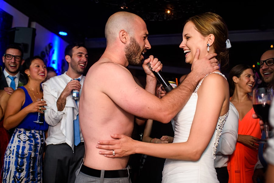 Shirtless groom sings to bride during wedding reception.