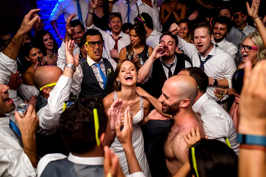 Bride and guests react to shirtless groom singing during wedding reception.