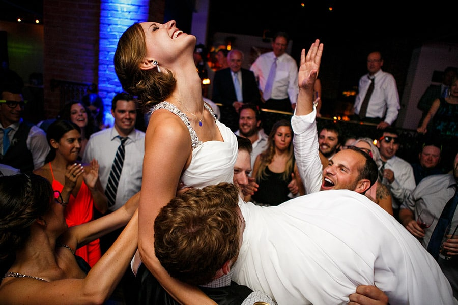 Bride is thrown into air during wedding reception.