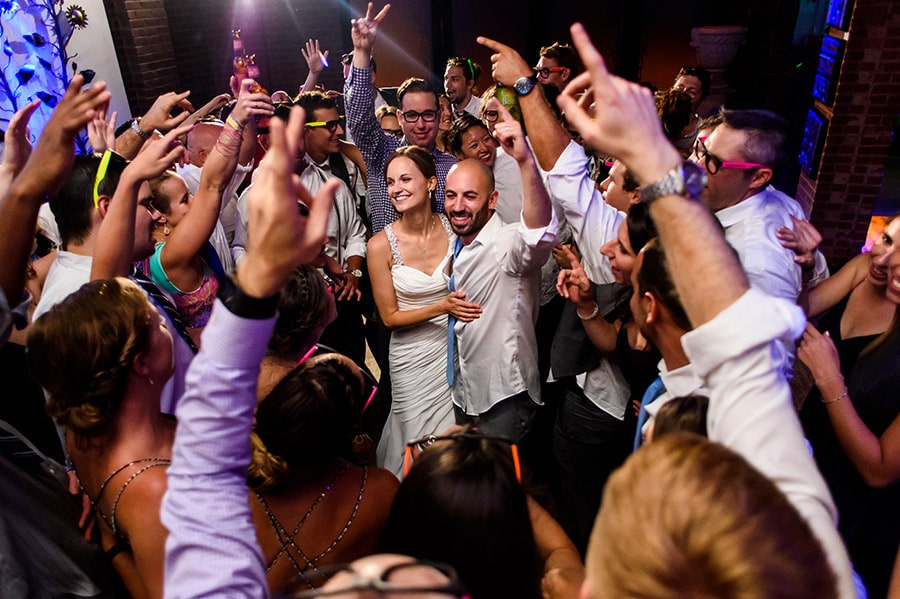 Wedding guests throw arms in the air as they surround bride and groom!