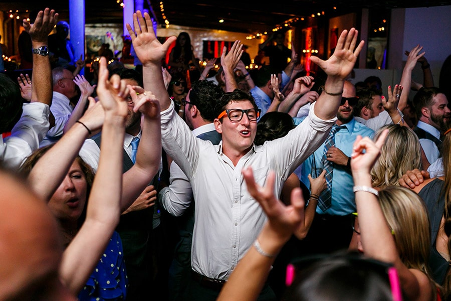 Wedding guest raises his arms like he just doesn't care.