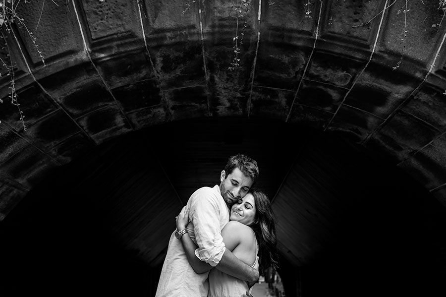 An engaged couple hug during their Central Park engagement.