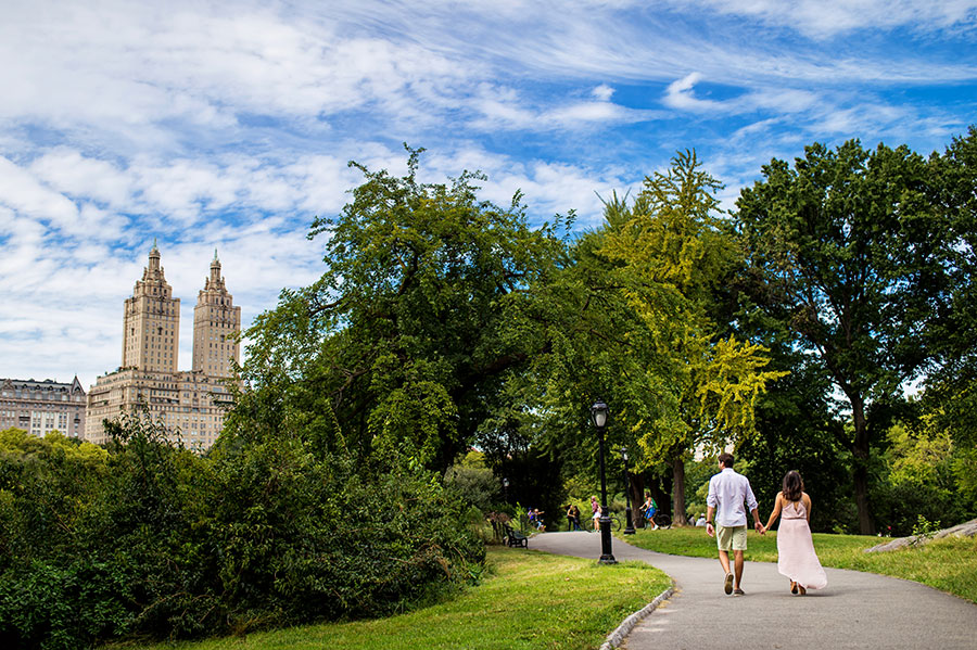 A Bride-to-be and Groom-to-be hold hands and walk through Central Park during their engagement session.
