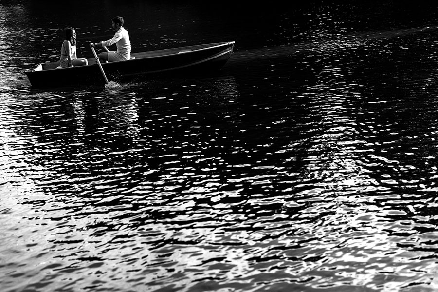 Engaged couple row in a boat in Central Park's lake.