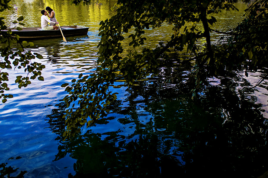 Woman kissed man in a boat on Central Park's lake during their engagement session.