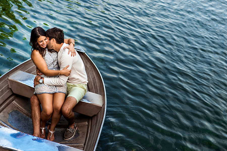 An engaged couple sit in a boat in Central Park during their engagement session.