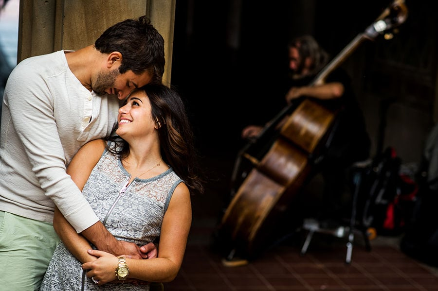 An engaged couple hug as a street performer plays Cello behind them during their engagement session in Central Park.