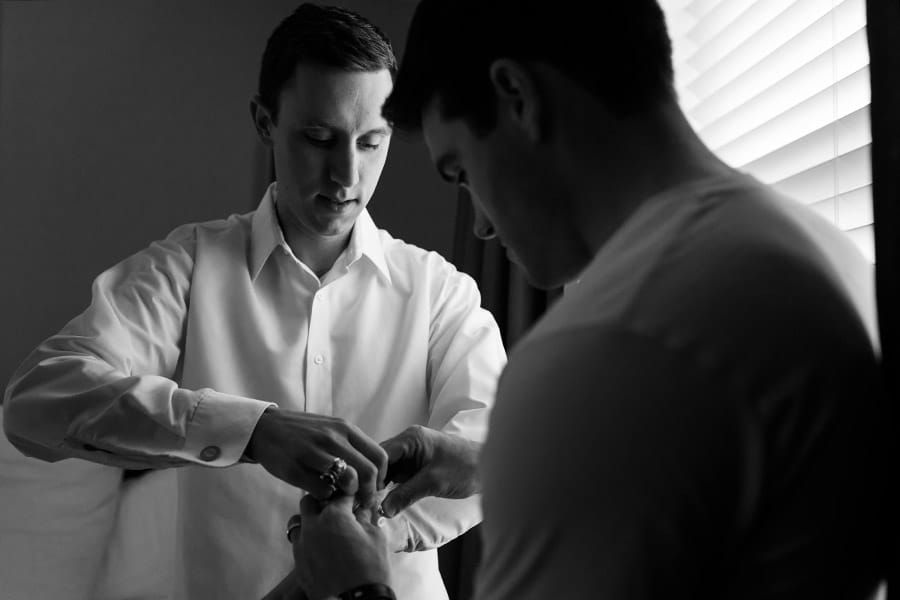 Best man helping groom with his cufflinks on his wedding day.