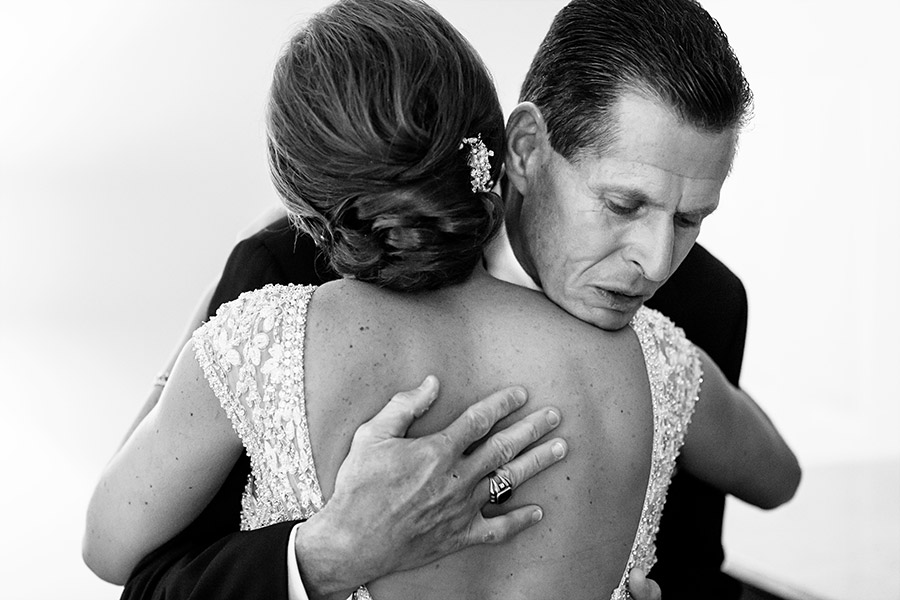 Father of the bride hugging his daughter for the first time in her wedding dress.