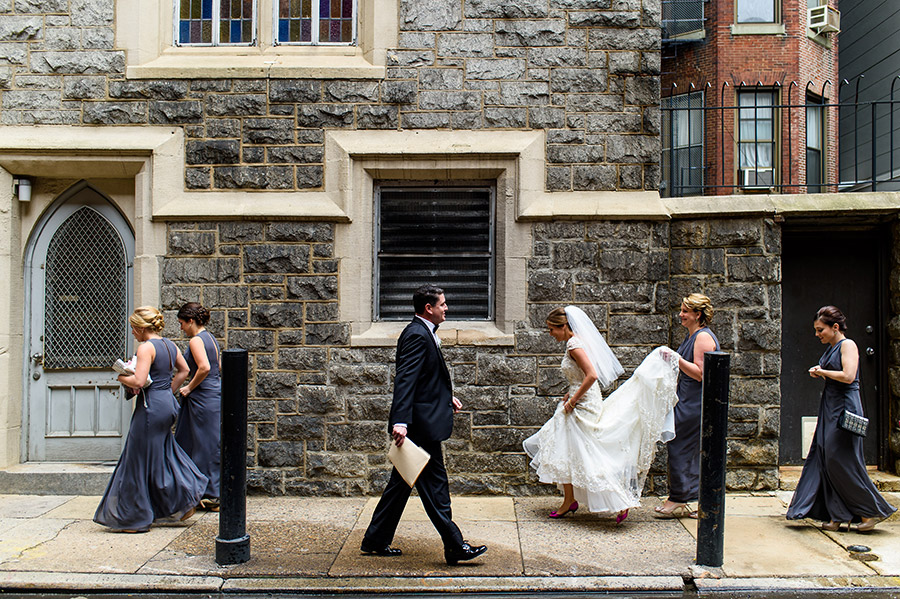 Bride and bridesmaids walk down rainy alley to church ceremony on wedding day.