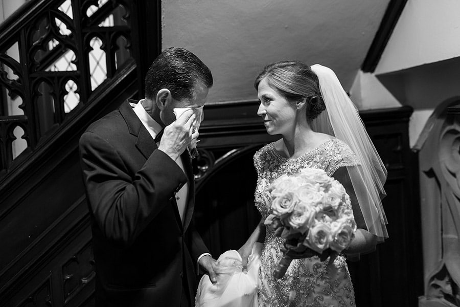 Bride looks at her father wiping tears away before wedding ceremony.