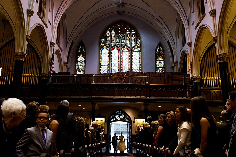 Father of the bride and bride enter the church to walk down the aisle in Philadelphia wedding ceremony.
