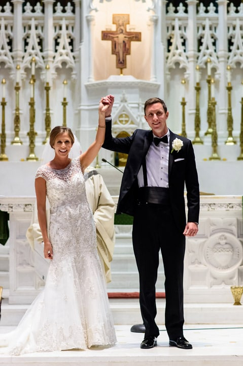 Bride and groom raise their arms and celebrate being named husband and wife.