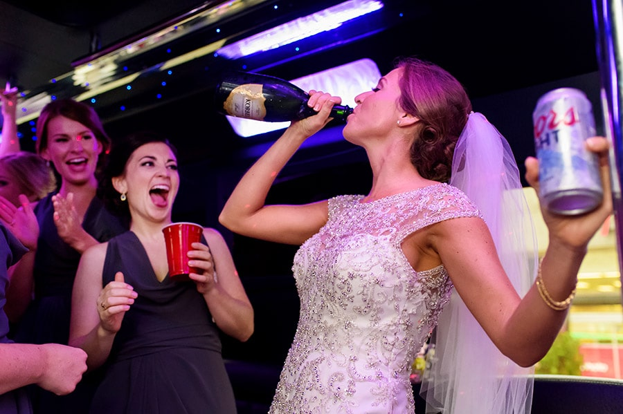 Bride chugs champagne on bus after wedding ceremony.