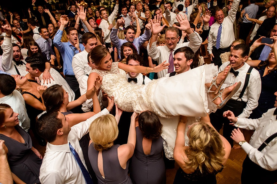 Bride crowd surfing on wedding guests shoulders during wedding reception!