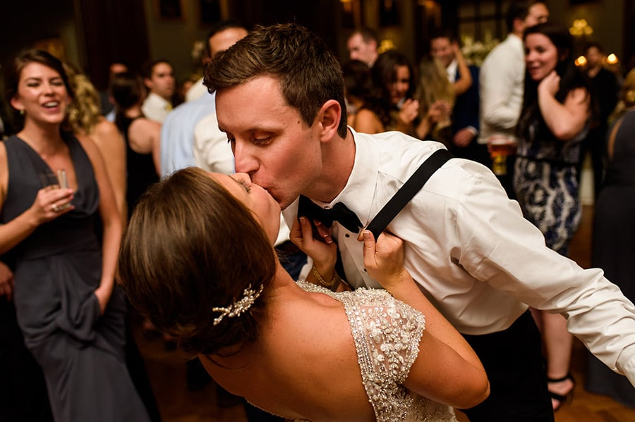 Bride pulling groom into kiss him by the suspenders!