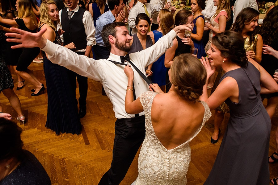 Bride dancing and pulling on groomsmen's suspenders during wedding reception!