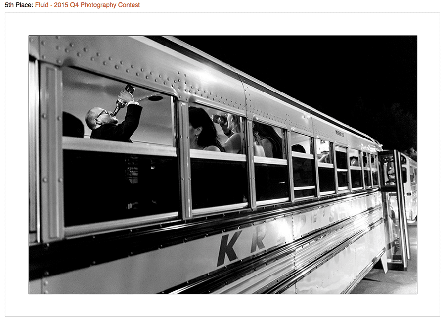 Contest winning photo of groomsmen chugging liquor on a school bus after wedding reception.