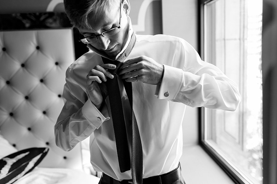 Groom tying his tie on wedding day.