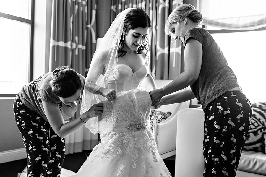 Bridesmaids helping bride put her dress on at Hotel Monaco in Philadelphia, PA.