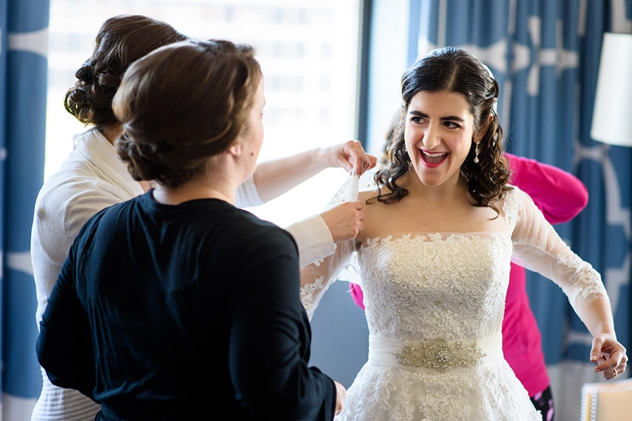 Excited bride putting a lace jacket on.