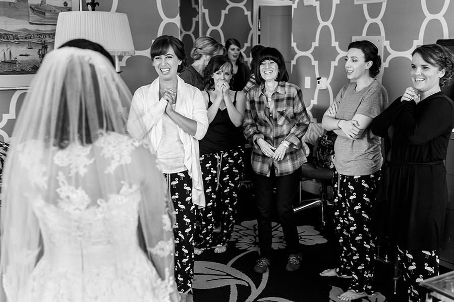 Mother of the bride and bridesmaids laugh and cry as they see bride in her dress for the first time.