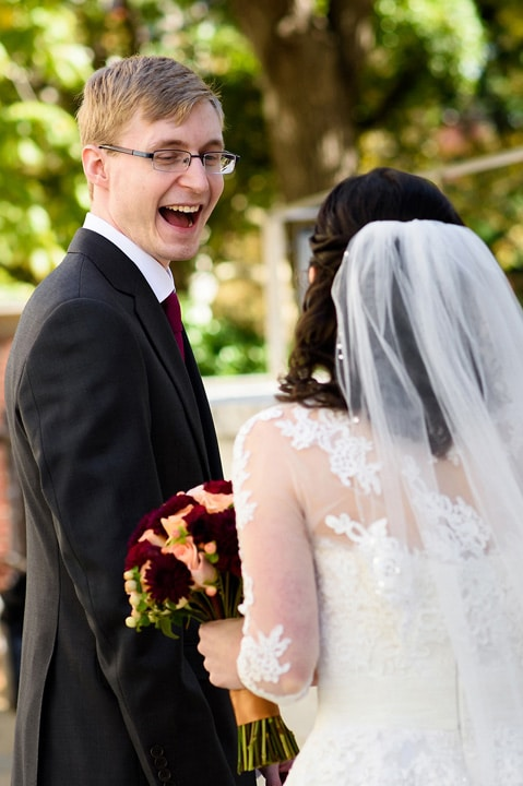 Excited groom seeing his bride for the first time at their first look.