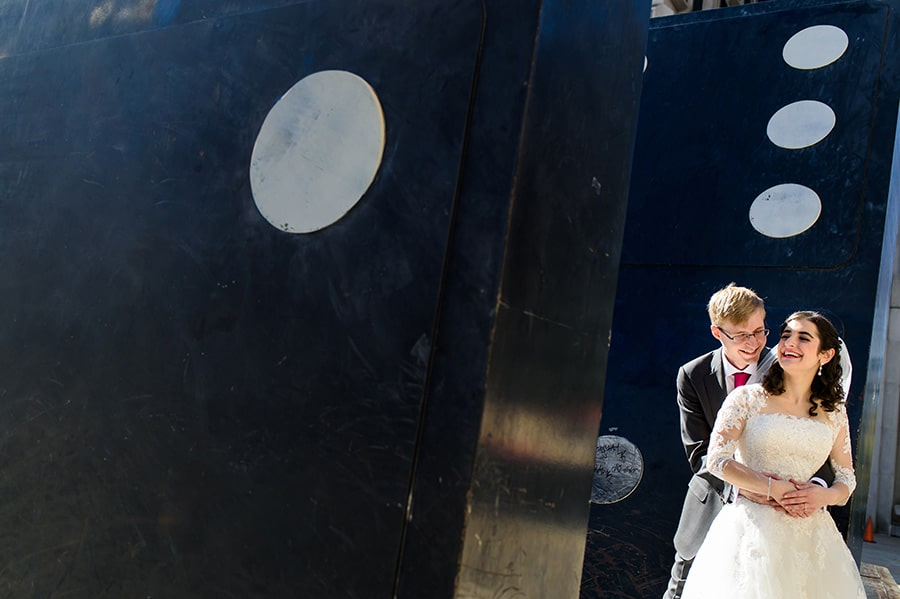 Bride and groom snuggling on giant domino game pieces in Philadelphia park near City Hall.