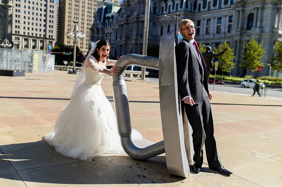 Bride ironing groom with giant Monopoly game piece in Center City Philadelphia.