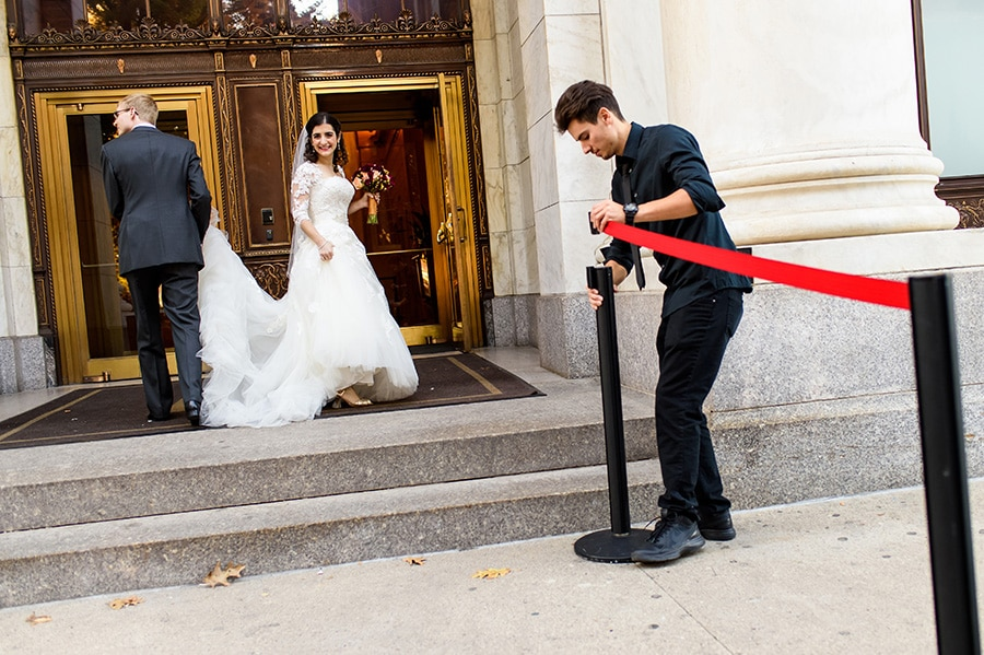 Bride and groom enter the Downtown Club as parking attendant puts out red tape.