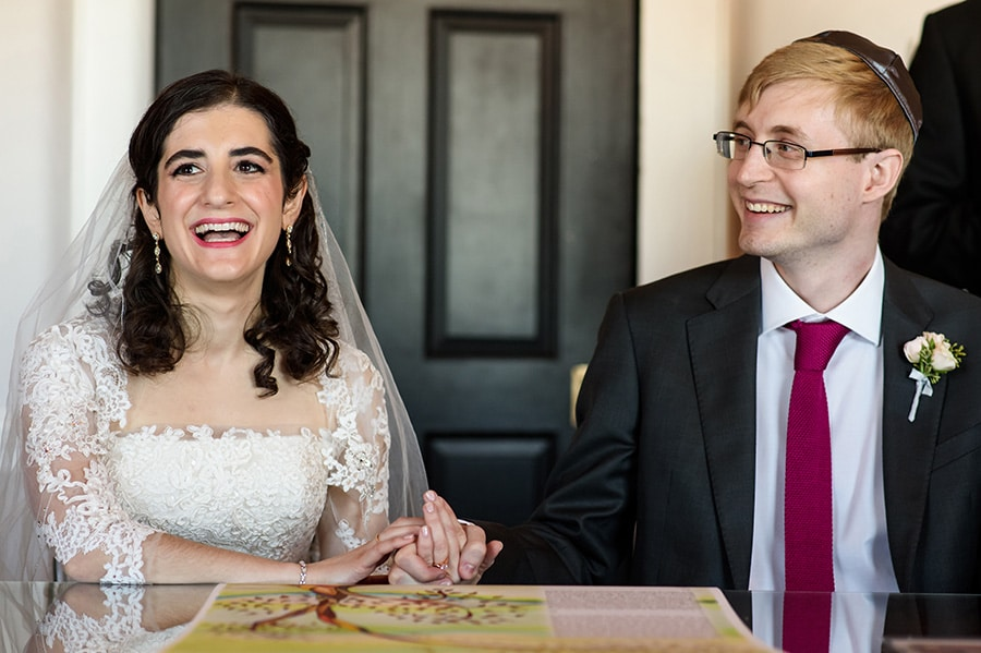 Excited bride and groom laugh as they sign their Ketubah.