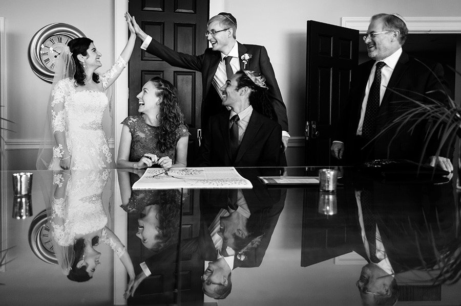 Excited bride and groom high-five as witnesses sign their Ketubah, a Jewish wedding tradition, during the wedding day.